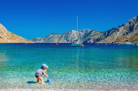 Unidentified kind spelen op azuurblauwe zee baai met jacht op achtergrond, Griekenland