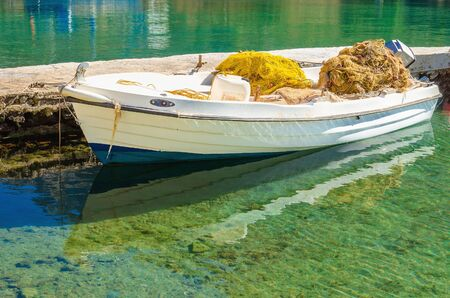 fishermans net: White boat with fishermans net in port with clear water