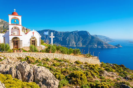 greek island: Iconic church with red roof on cliff over sea bay on Greek island, Greece