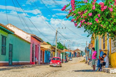 TRINIDAD, CUBA - 08 de diciembre 2013: Púrpura y blanco clásico coche americano y edificio colonial azul en calles de Trinidad, donde los coches viejos son reliquias de la revolución cubana y todavía atrae a los turistas.