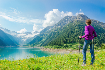 A young mountaineer stands beside an azure mountain lake on the background of the high peaks of the Alps, Zillertal, Austria Stock Photo