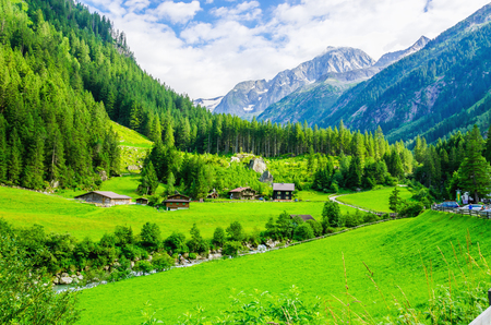austrian village: Beautiful alpine landscape with green meadows, alpine cottages and mountain peaks, Zillertal Alps, Austria Stock Photo
