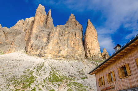 refuge: Wooden shelter rifugio with shutters below Tre Cime peak in Sexten Dolomites, Italy