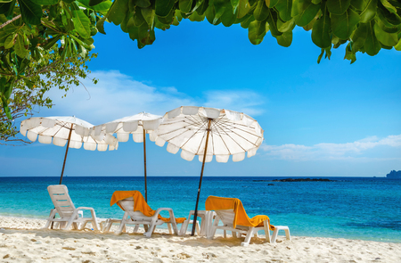 thailand culture: Sunbeds with orange towels under white umbrellas on sandy beach, Phi Phi Island, Phuket area, Thailand Stock Photo