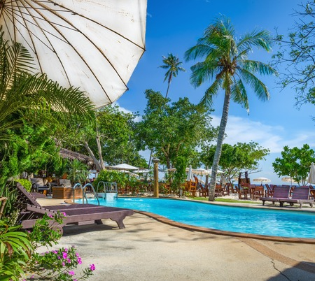 bali province: White sun umbrella at azure swimming pool with wooden sunbeds, Phi Phi, Phuket, Thailand Editorial