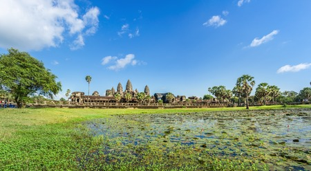 historic site: Angkor Wat Temple in sunny day across lake, Siem reap, Cambodia.
