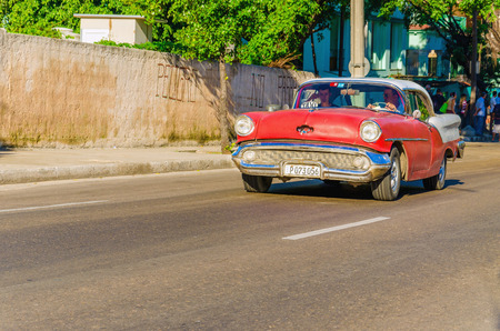 american revolution: HAVANA, CUBA - DECEMBER 2, 2013: Classic American red car one of streets in Havana, where old cars bought before Cuban revolution are icon view of Cuba