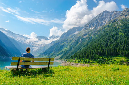 Een jonge man zit op een bankje naast een azuurblauwe bergmeer op de achtergrond van de hoge toppen van de Alpen, Zillertal, Oostenrijk