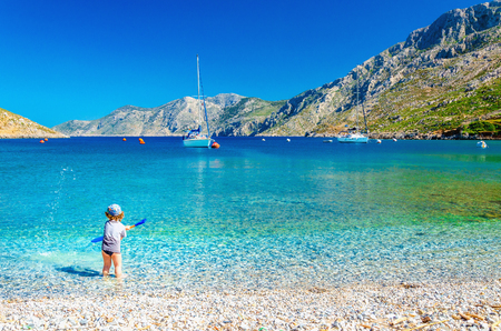 greece shoreline: Amazing sea bay on Greek Island with a small boy at play on the seashore, Greece