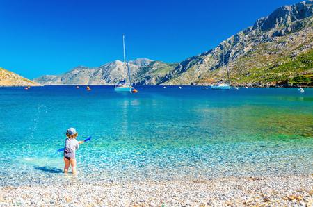 Prachtige zee baai op Grieks eiland met een kleine jongen in het spel aan de kust, Griekenland