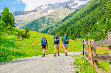 friends: Young mountaineers on the background of alpine landscape, green slopes and high mountain peaks, Austria, Alps Editorial