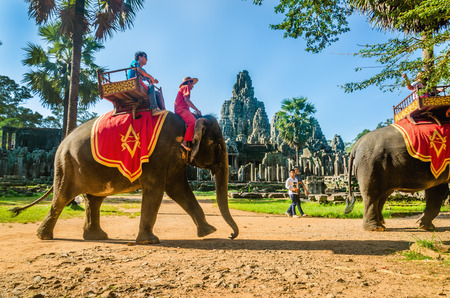 CAMBODIA, SIEM REAP - NOVEMBER 2, 2014: Tourists ride an elephant on a howdah chair, at the Bayon temple area of Angkor Wat, near Seam Reap, Cambodia Éditoriale