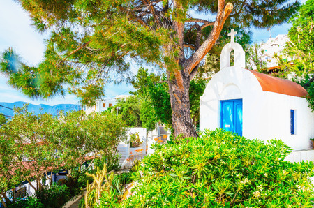 Small white Greek church with blue doors typical for Greek island culture, Greece