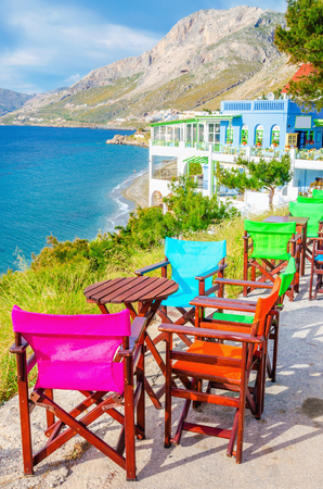 ionian island: Colorful wooden chairs with view on sea bay on Greek Island, Greece