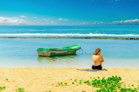 martinique: SRI LANKA, BERUWALA - JANUARY 9, 2015: Exotic beach with young girl, fishing boat and azure water, Sri Lanka, southern Asia