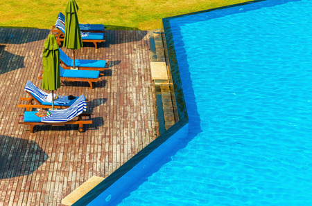 martinique: Luxury swimming pool with blue sun loungers and green sunshades Editorial