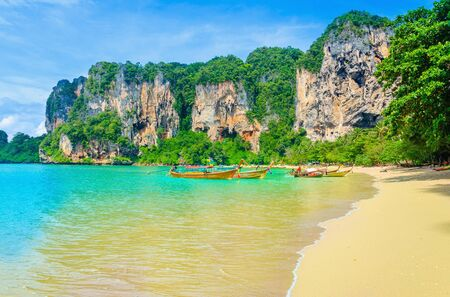 ao: Amazing Railay Beach with mogotes, long tail boat andred kayaks, Krabi, Thailand