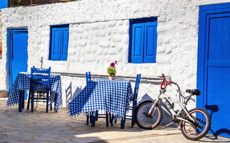 KALMNOS, GREECE- MAY 1, 2015: Typical Greek restaurant with blue tables and chairs and small bike parked