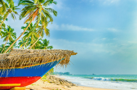 southern sri lanka: Exotic beach with colorful boat, tall palm trees and azure water, Sri Lanka, southern Asia Stock Photo