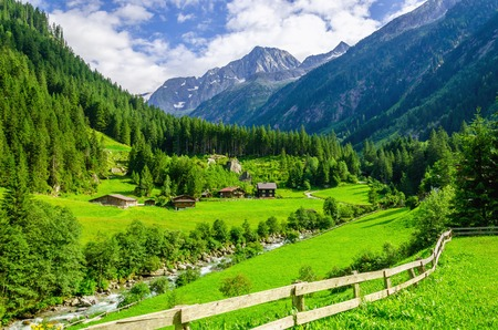 Beautiful alpine landscape with green meadows, alpine cottages and mountain peaks, Zillertal Alps, Austria Standard-Bild
