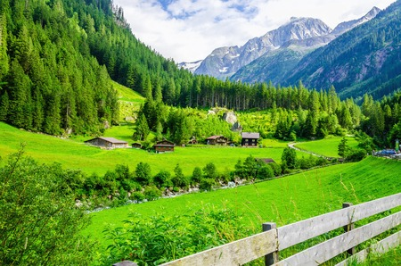 green meadows: Beautiful alpine landscape with green meadows, alpine cottages and mountain peaks, Zillertal Alps, Austria Stock Photo