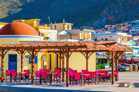dinner cruise: Colorful restaurant with red wooden chairs in small Greek town with typical buildings Editorial