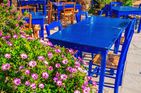 greece: Blue tables in colorful Greek restaurant with a lot of flowers, Greece
