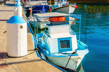 samll: Very samll wooden boat painted in Greek blue and white colors in port