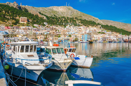 greek island: White boats in small cosy port on Greek Island with clear blue water Stock Photo