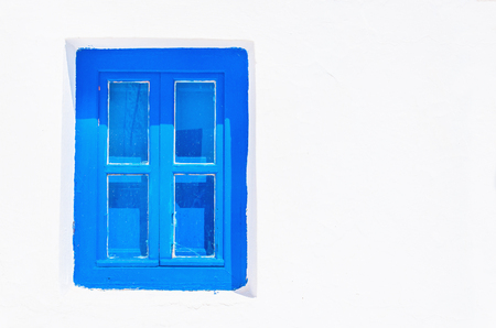 against white: Iconic blue wooden window against clear white wall. Typical view for Greek islands, Greece