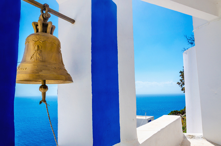bell: Iconic view on golden bell and typical blue-white church on Greek Island Kalymnos, Greece