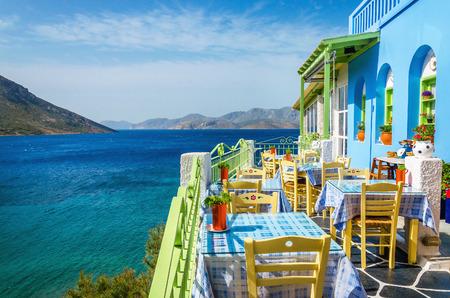 Typisch Grieks restaurant op het balkon blauwe gebouw met uitzicht op de zee, Griekenland Redactioneel