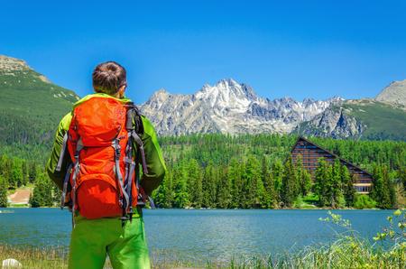 Young man with an orange backpack admire the beauty of a mountain lake, Strbske Pleso, High Tatras, Slovakia