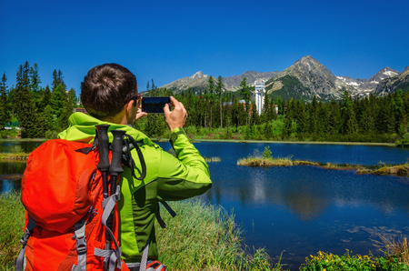 mountaintops: A young man takes a picture mountaintops and beautiful mountain lake