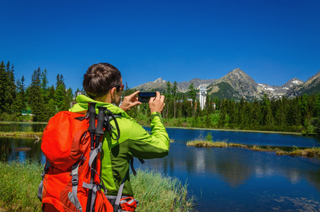mountaintops: A young man takes a picture mountaintops and beautiful mountain lake Strbske Pleso in National Park High Tatra, Slovakia, Europe