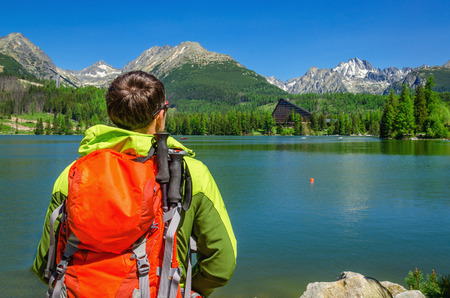 admires: Young man admires the view of high mountains and mountain lake in National Park High Tatra, Slovakia, Europe Stock Photo