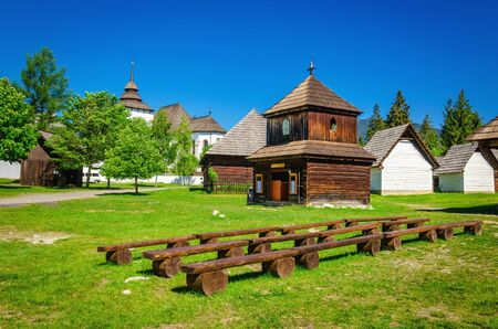 liptov: Rare wooden bell tower with folk houses in open-air museum of Liptov, Pribylina, Slovakia Stock Photo