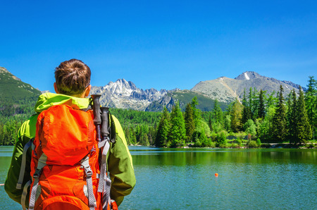british columbia: Young man admires beautiful view of the mountain lake Strbske Pleso in National Park High Tatra, Slovakia, Europe