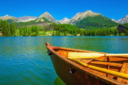산의 높은 봉우리의 배경에 아름 다운 산 호수에 목조 보트