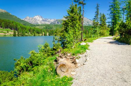 plitvice: Path next to a beautiful mountain lake with stones