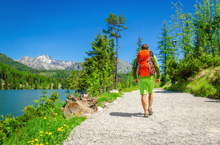 sports attire: Young man in sports attire goes a path next to a beautiful mountain lake Stock Photo