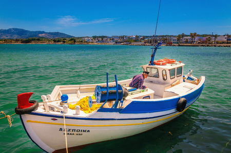 KALYMNOS, GREECE - MAY 01, 2015: Traditional fishing Greek boat with fisherman on the background of azure water and blue sky