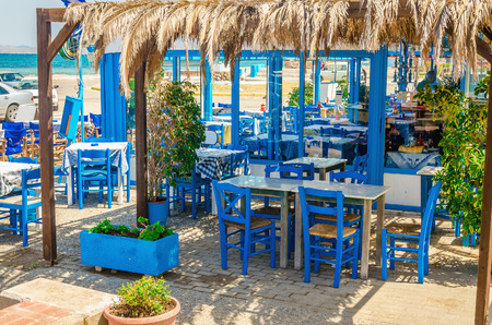 Romantic Greek restaurant with blue chairs and tables under palm leaves, Greece