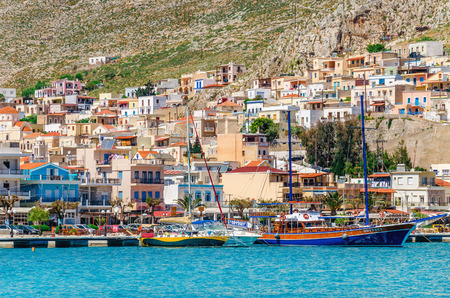 KALYMNOS, GREECE - MAY 01, 2015: Wharf and cosy traditional Greek boats , old wooden ships and yachts in port of Pothia, Kalymnos, Greece