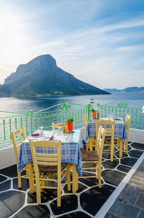 mykonos: Tables at Greek restaurant with tableclothes in national Greek colors and view on sunset at see, Greece