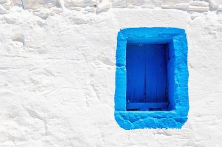 Iconische blauwe houten raam op een witte stenen muur van typisch Grieks huis, Griekenland