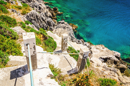 greek island: Green bushes and stairs to the beach with clear water of Aegan Sea on Greek island, Greece