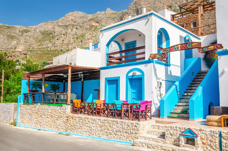 KALYMNOS, GREECE - MAY 01, 2015: Panoramic view on typical Greek modern blue and white restaurant with colorful chairs and tables, Greece