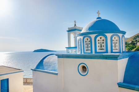 view on sea: Typical Greek church with iconic blue dom and view on Aegean sea in sunny day, Greece