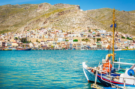 KALYMNOS, GREECE - MAY 01, 2015: Blue boat moored in peaceful port on Greek Island, Greece